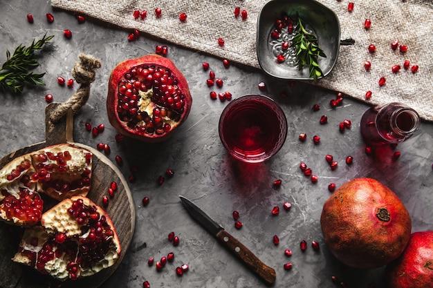 Красный гранатовый сок в стакане, спелый и разрезанный гранат и веточка мяты на сером фоне бетона. концепция витаминов, антиоксидантов и здорового питания. заложить квартиру. вид сверху.