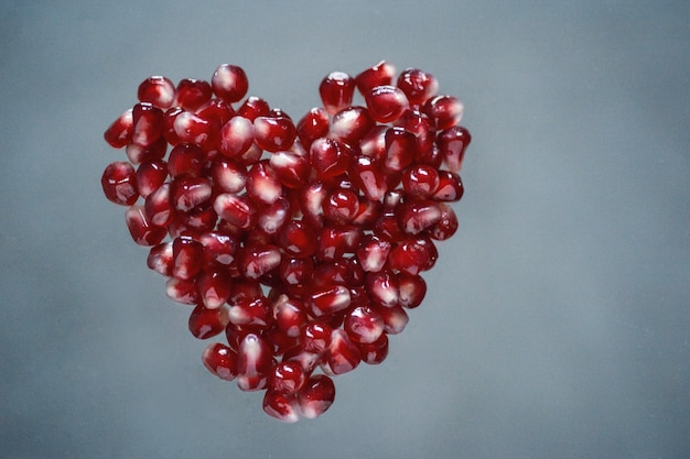 Red pomegranate seeds in heart shape