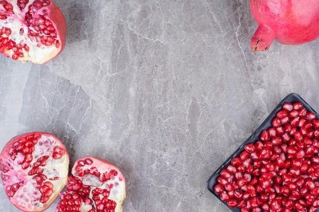 붉은 석류와 돌 배경에 씨앗 접시.