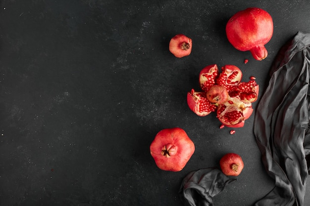 Red pomegranates on black tablecloth and surface.
