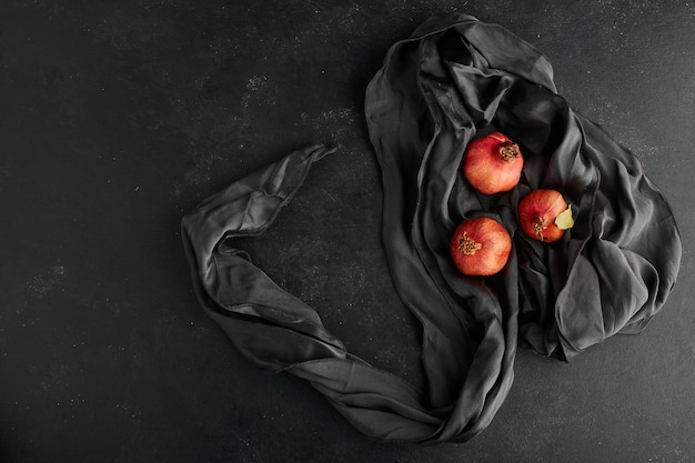 Red pomegranates on black tablecloth, top view.