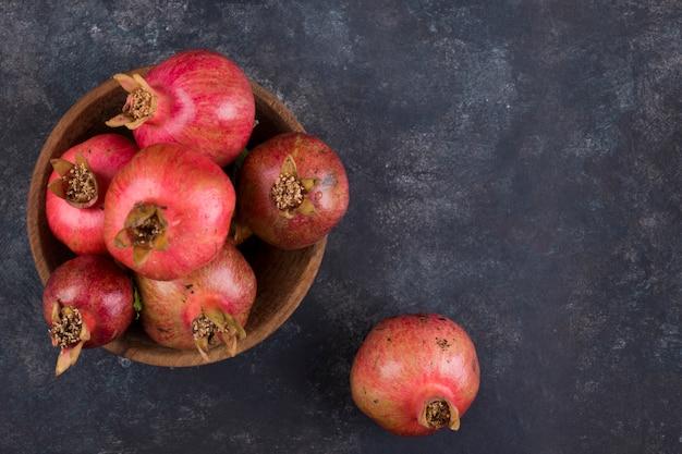 Красные гранаты на деревянном блюде на мраморе, вид сверху