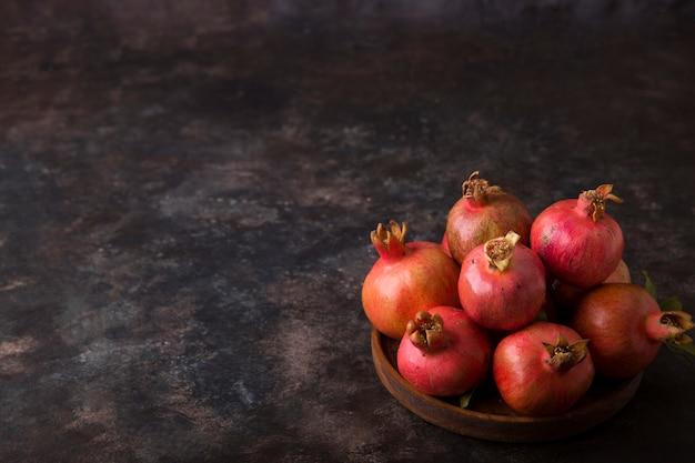大理石の木製の大皿に赤いザクロ