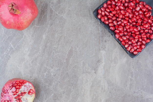 Red pomegranates and plate of seeds on stone background.