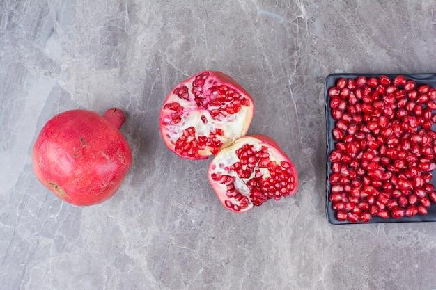 Melograni rossi e piatto di semi su fondo di pietra.