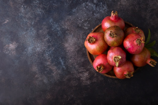 Red pomegranates in a platter on black table