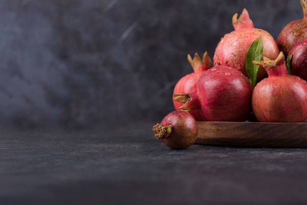 Red pomegranates in a wooden platter on marble