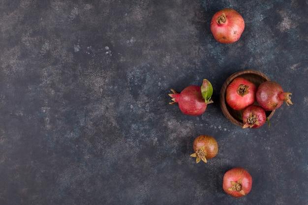 Melograni rossi in un piatto di legno, vista dall'alto
