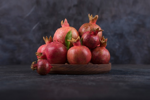 Melograni rossi in un piatto di legno