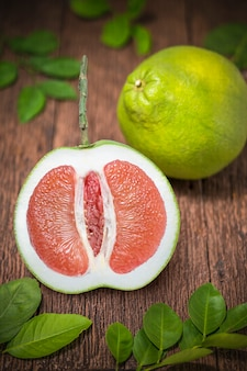 Red pomelo fruit with leaves on the old wooden table.