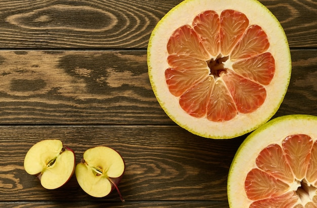 Red pomelo halves and apple halves on a wooden table