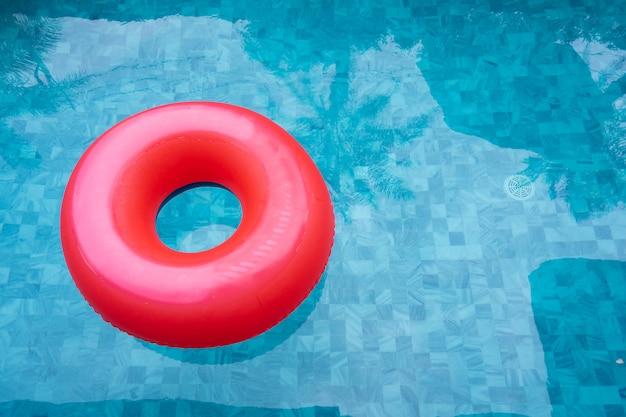 Красный бассейн плавать, кольцо плавает в освежающий голубой бассейн с тенью кокосовой пальмы.