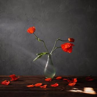 Красные маки в вазе на деревянном столе