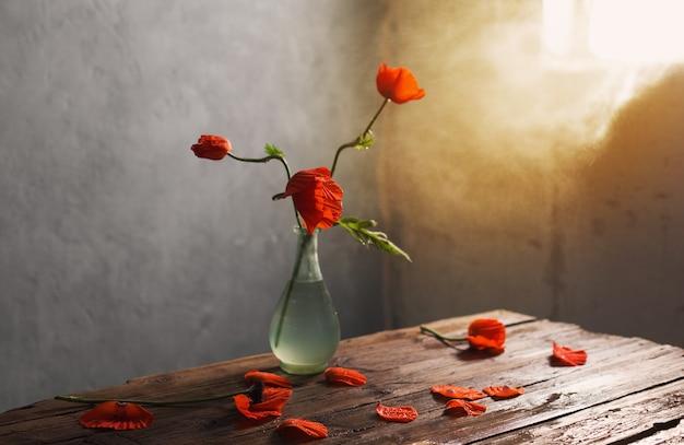 나무 테이블에 꽃병에 빨간 양 귀 비