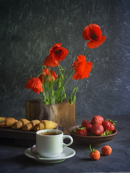 Red poppies in a wooden vase, a cup of coffee, strawberries in a plate and croissants
