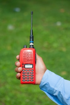 Red portable radio transceiver in hand