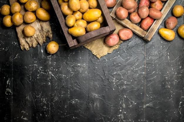 트레이에 빨간 감자와 상자에 노란색 감자. 블랙 소박한