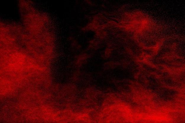黒の背景に赤い粉塵爆発の雲。飛散する赤色のほこり粒子の凍結運動。