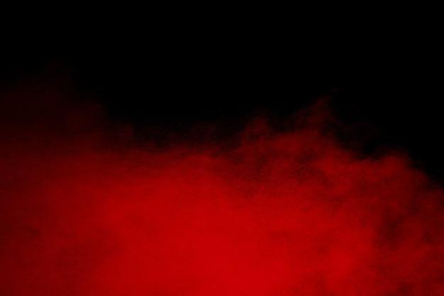 Облако взрыва красного порошка на черном фоне.