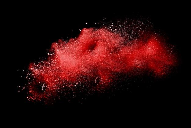 黒の背景に分離された赤い粉の爆発