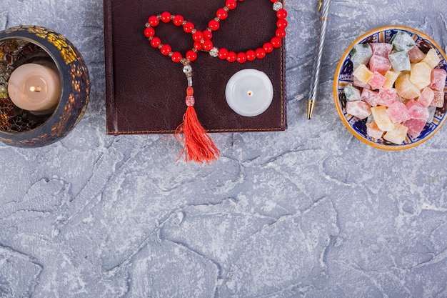 Red prayer beads; candle; diary; pen; lighted candle with bowl of rakhat-lukum on rough grey textured background