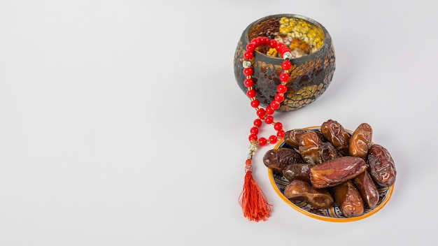 Red prayer beads with fresh juicy palm dates on white background