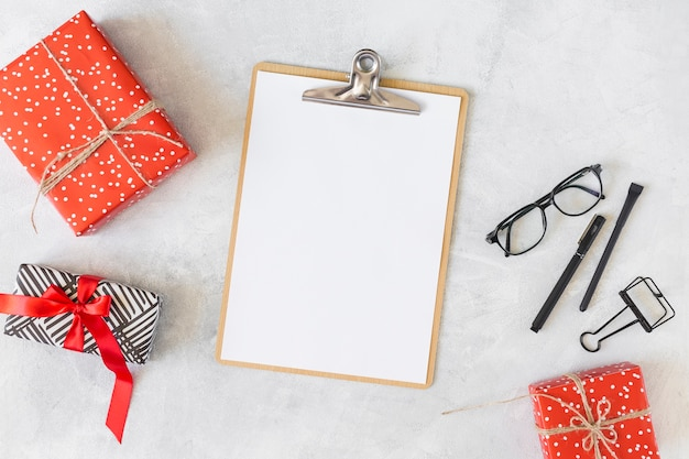 Red present boxes, eyeglasses, clipboard and pens