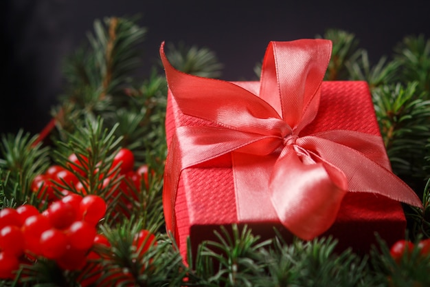 Red present gift box with satin pink bow, immersed in the needles of a christmas tree decorated with red berries.