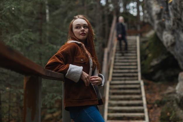 橋の手すりにもたれて立っている茶色のジャケットの赤、かわいい女の子