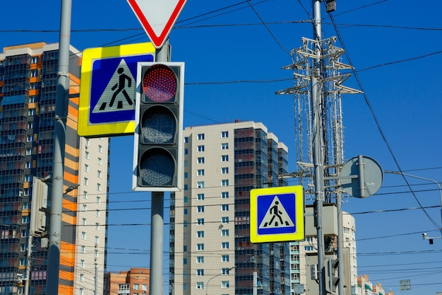 Red prohibition signal of traffic light on the background of highrise buildings