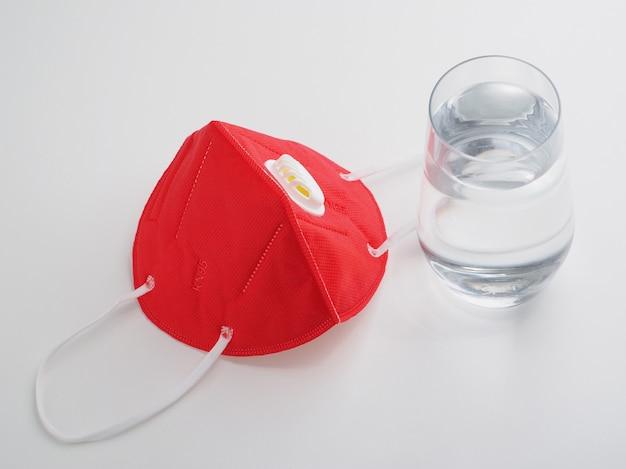 赤い保護マスクと白い机の上の水のガラス。