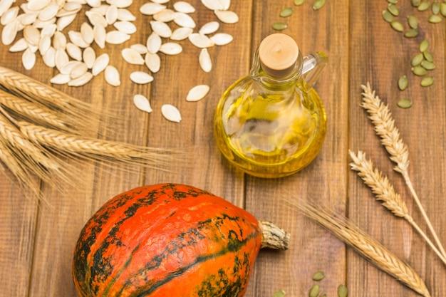 赤いカボチャとオイルのボトル。テーブルの上のカボチャの種と小麦の小穂。木製の背景。フラットレイ。