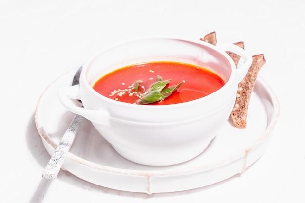 Красный суп-пюре с помидорами, зеленью и хлебом. модный жесткий свет, темная тень. белый фон шпатлевки, крупным планом