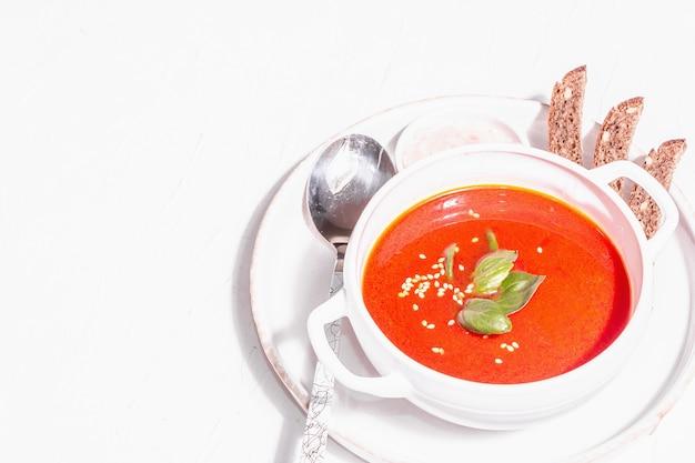 Красный суп-пюре с помидорами, зеленью и хлебом. модный жесткий свет, темная тень. белый фон шпатлевки, копия пространства
