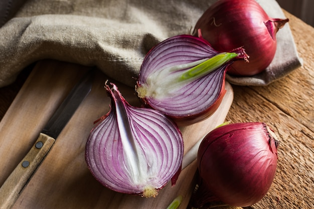 Red or purple onion cut in half, wood breadboard, linen towel, knife