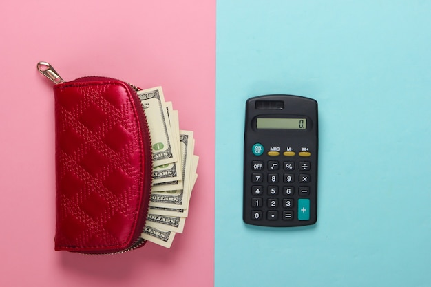 Красный кошелек со стодолларовыми купюрами и калькулятором на сине-розовой пастели.