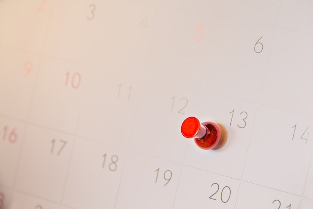 Red push pin on calendar page for remind and marked important events day