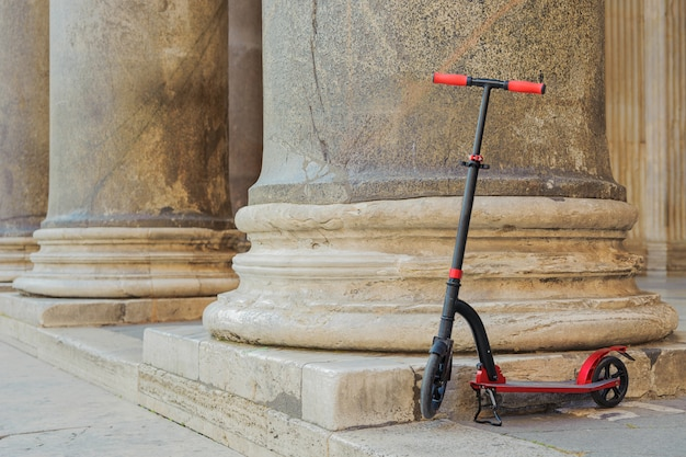 Red push scooters against the backdrop of the colonnade pantheon in the roma, italy.