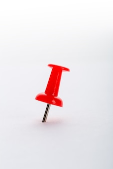 Red pushpin closeup isolated on white