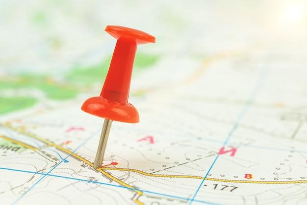 Красная канцелярская кнопка на карте города, концепция путешествий и назначения, фоновое фото