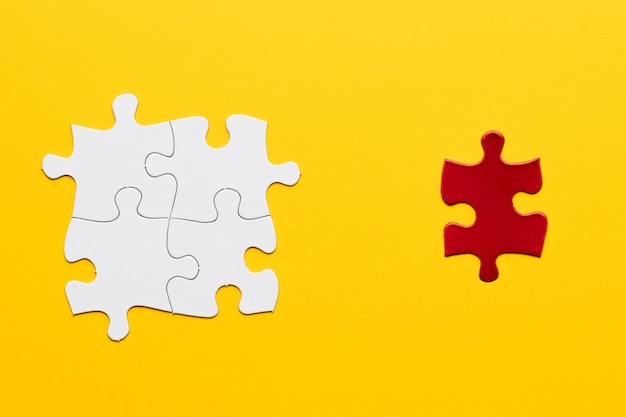 Red puzzle piece standing separately from white puzzle piece on yellow backdrop
