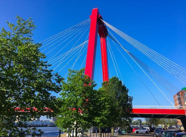 ロッテルダムオランダのニューウェマース川に架かるウィレムスブルグ橋の赤いパイロンとケーブル