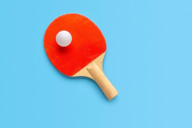 Красная ракетка для настольного тенниса с шариком на голубой стене. пинг-понг спорт