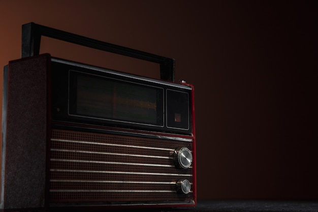 어두운 배경에 빨간색 라디오입니다. 빈티지 스타일 색상으로 촬영하고 톤의 오래된 복고풍 물건을 닫습니다.