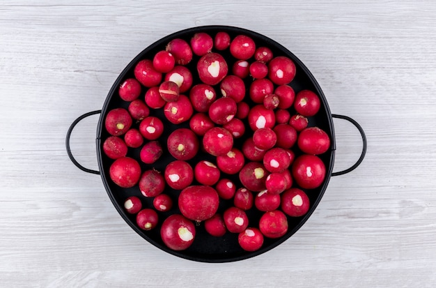 Red radish in a black pan on white wooden table. flat lay.