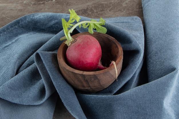 Красный редис в деревянной миске с тканью
