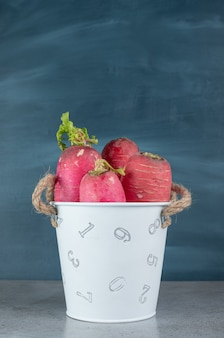 Red radish and leaves in on a gray background. high quality photo