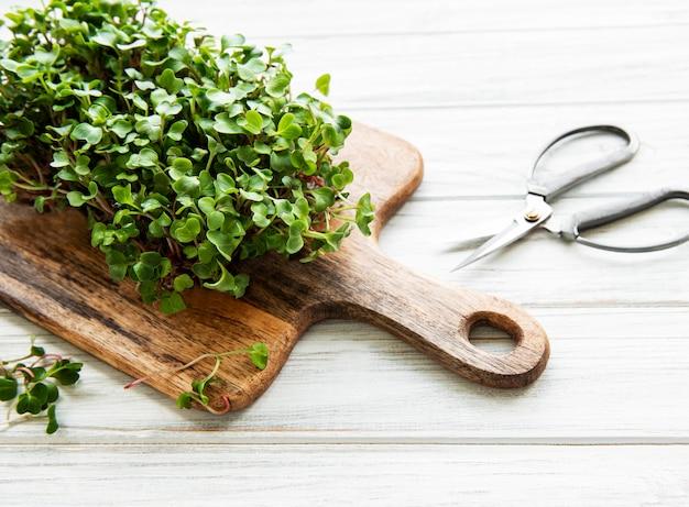 Microgreens красной редиски на деревянной разделочной доске, здоровая концепция