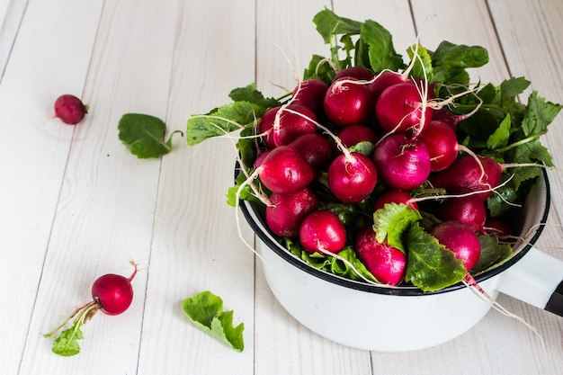 Red radishes in bowl on wood table