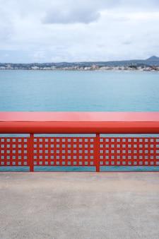 바다 앞의 빨간 난간. 잔잔한 바다와 흐린 날. 사각 구멍이 있는 난간. 알리칸테, 자바